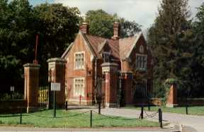 A red brick lodge building next to ornate wrought iron gates.