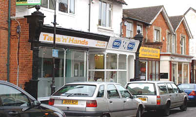 two shops with a single storey frontage protruding from a white painted building.