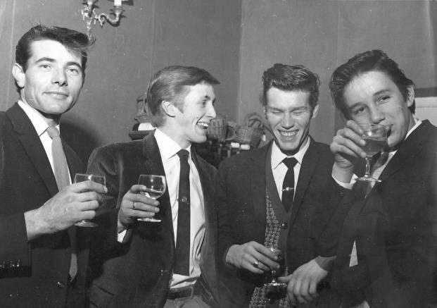 four young men wearing smart ties and jackets and holding wine glasses.
