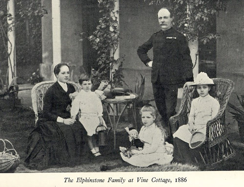 3 children in white all seated, 2 adults in black, a lady seated and a man standing.  Dated 1866.  All in period costume.