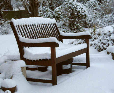 wooden garden seat covered in snow