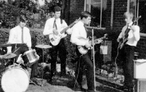Four teenagers wearing white shirts and ties playing guitars and drums.