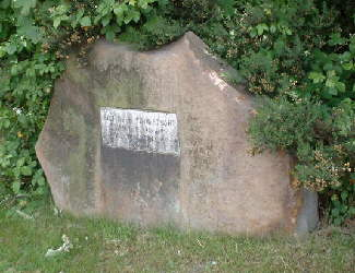 A large flat stone mounted on its edge and with a plaque on it