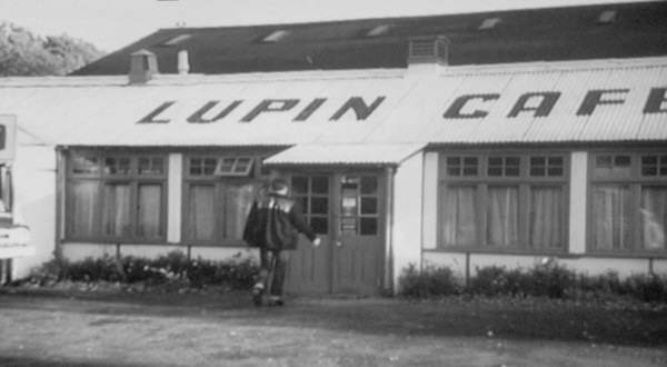 A long low building with a corrogated roof with LUPIN CAFE painted on it.