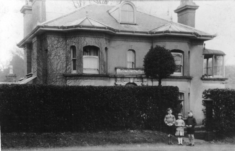 3 small children standing in front of a large hedge with an old double-fronted building behind