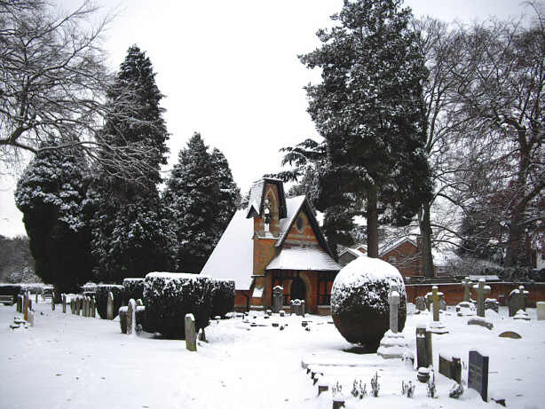 red brick building and grave stones in snow.