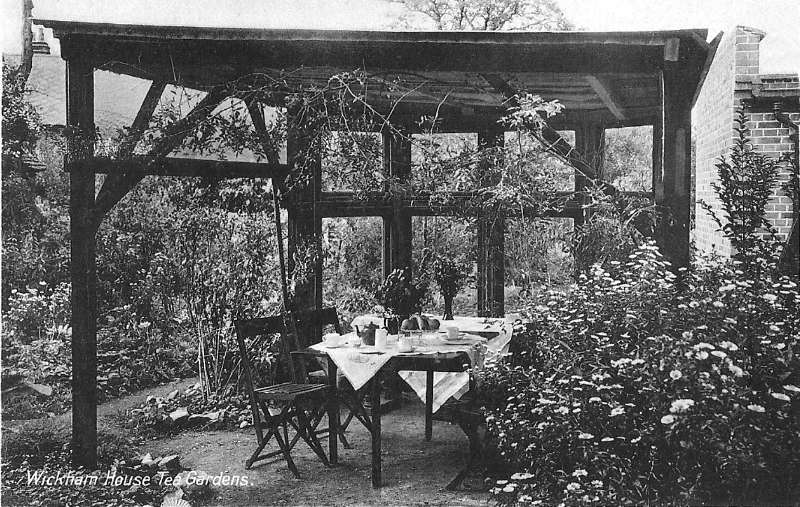 Table and chairs set below a wooden framework in a garden setting