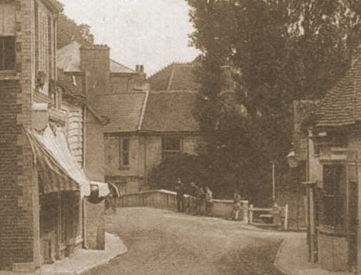 An old sepia photo showing a narrow unpaved street between two buildings, turning to the left over a bridge and with a large, obviously extended, building beyond.