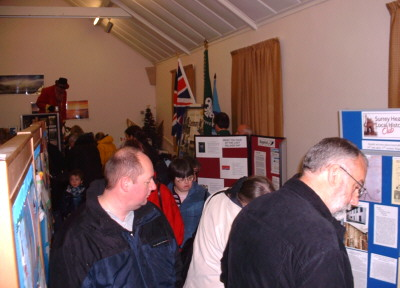 people looking at display stands featuring scouts, guides and a local history club.