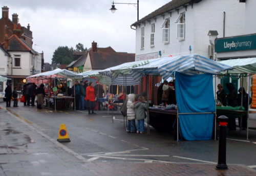 market type stalls in a road. wet road surface. various covers held up as protection from the weather.