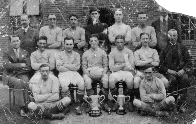 a formalpose of a football team in their playing strip, plus smartly suited men and two trophies.