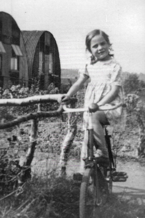 a girl on a bicycle in front of two huts with semi-circular roofs