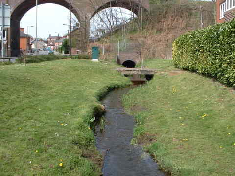 a stream meandering through a grass sided hollow with a railway viaduct in the background
