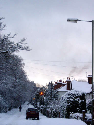 a drab snow scene of a road going off into the distance with houses onits right hand side, smoke coming from one of the chimnies and  alone pedestian walking
