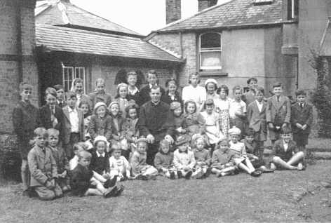 a large formal group of children together with a priest