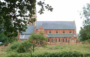 red brick church building with grass and trees in front