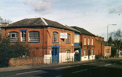 a red brick building with large blue doors fronting onto a main road