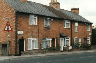 A row of four small brick built cottages.