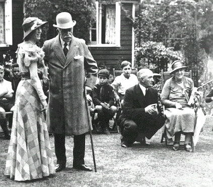 A B&W photo of a lady in an elaborate dess and hat, together with an elderly man wearing an overcoat and bowler hat, supporting himself with a walking stick. Seated is an older lady with a man squatting talking to her. Behind are children sitting on wooden chairs, at least one wearing Wolf Cub uniform.